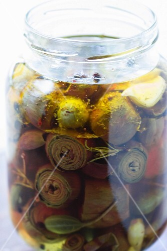 Pickled baby artichokes in a jar with caper fruits, bay leaves and rosemary