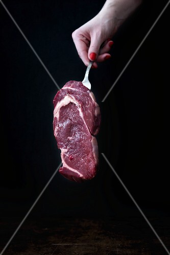 A woman hold a raw beef steak on a fork