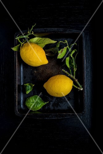 Two lemons with leaves in a black bowl