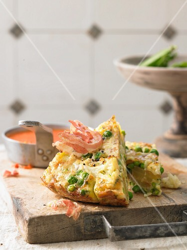 Cauliflower frittata with wild flower cheese and bacon chips on a red pepper sauce