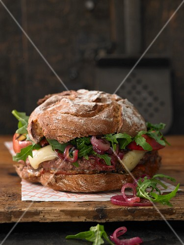 A brown bread burger with mountain cheese, minced lamb, grilled apple and sweet and sour onions