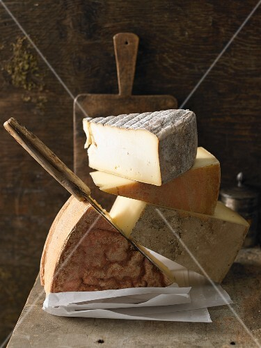 A stack of various hard cheeses with a knife