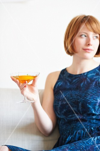 A woman drinking a cocktail at a party