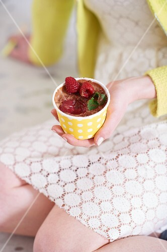 A woman holding a tub of chocolate muffin ice cream with raspberries