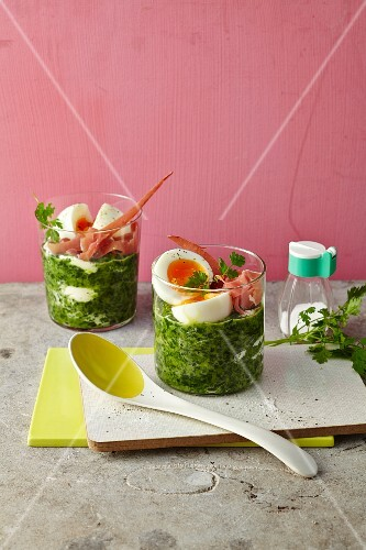 Eggs in glasses on ham and spinach
