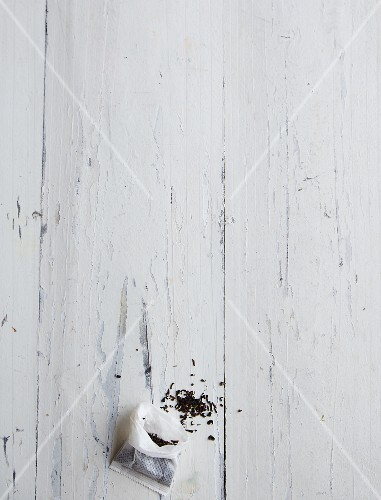 An open teabag and scattered tea leaves on a white wooden surface