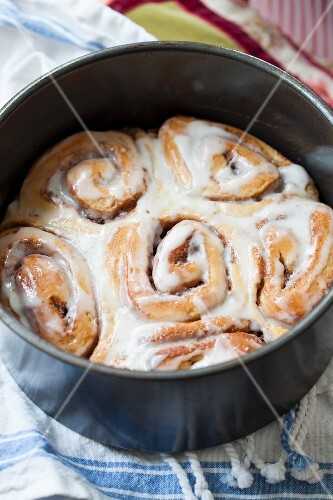 Cinnamon buns with pecan nuts and butter glaze in a baking tin
