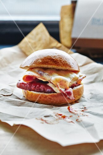 A bacon and cheese burger on a piece of paper