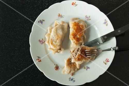 Fried pierogi (Polish meat dumplings) on a floral patterned plate