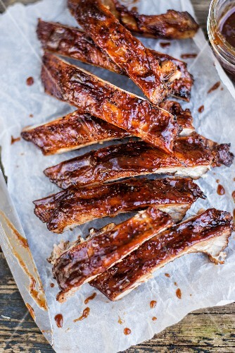 Spicy pork ribs with Bourbon barbecue sauce on paper (close-up)