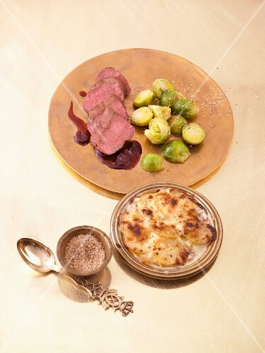 Venison fillet with Brussels sprouts and sesame seed salt, potato gratin and cranberry sauce