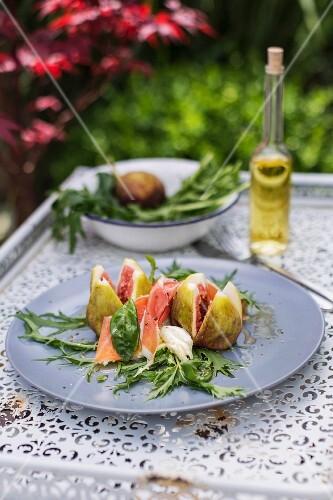 Fig salad with mozzarella, Serrano ham and basil on mizuna