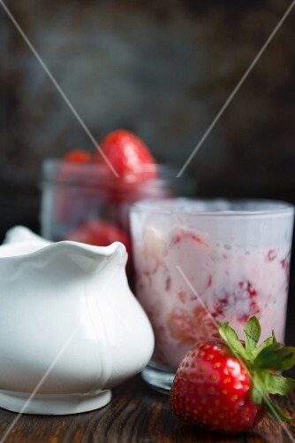 Strawberries with cream in a glass, fresh strawberries and a jug of cream