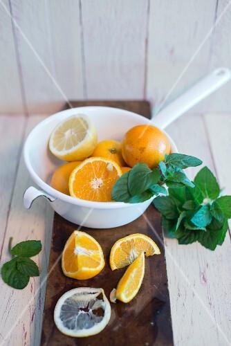 Oranges and lemons in an enamel colander, fresh mint and sliced oranges and lemons on a board