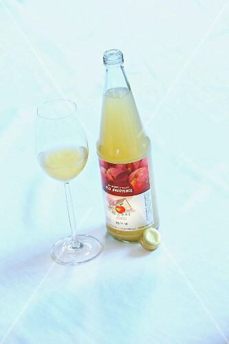A bottle of 'Red Jonaprince' apple juice and a glass of apple juice