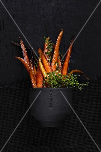Caramelized carrots with thyme in a black bowl