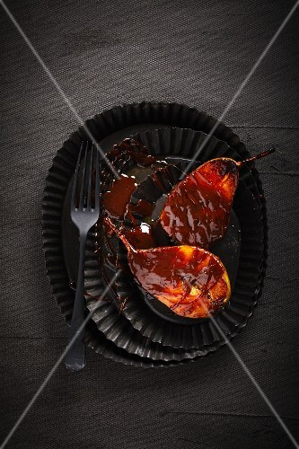Chocolate-glazed pears on a black plate (seen from above)