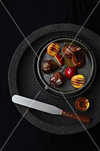 Grilled plums and pears on a black plate