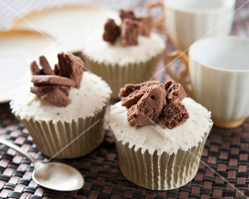Chocolate cupcakes decorated with frosting and chocolate biscuits