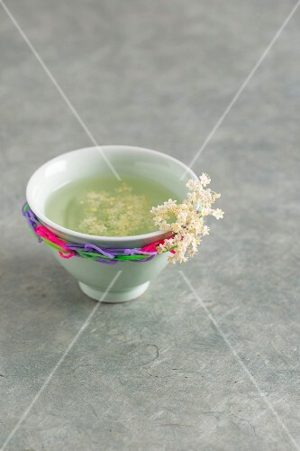 A tea bowl of elderflower tea decorated with rubber bands