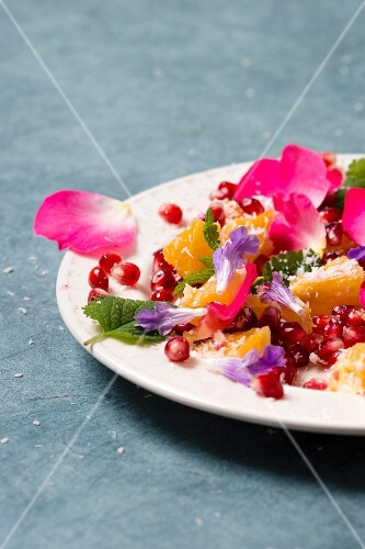 Orange and pomegranate salad with rose petals, sage flowers, lemon balm and grated coconut