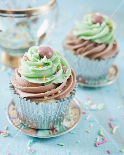 Cupcakes with chocolate and lime frosting decorated with chocolate beans and sugar sprinkles