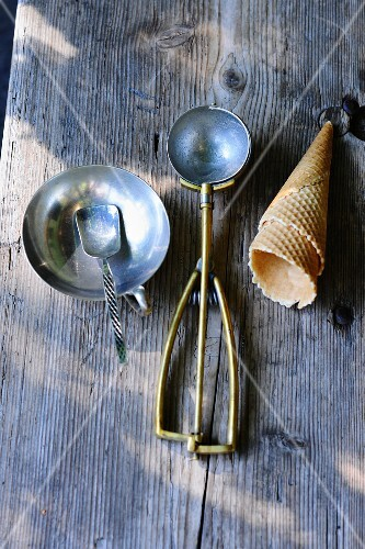 Ice cream cones, an ice cream scoop and an ice cream bowl with a spoon