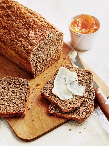 A loaf of wholemeal bread with butter and marmalade