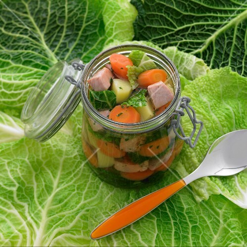 Vegetable stock with salmon in a preserving jar on a savoy cabbage leaf