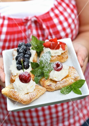A woman serving puff pastries with cream cheese and fruit
