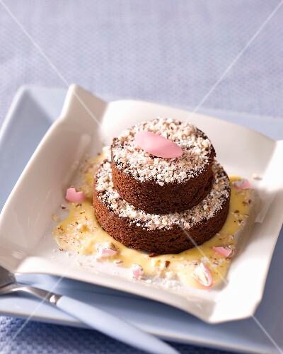 A two tier, mini chocolate sponge cake with almond sauce