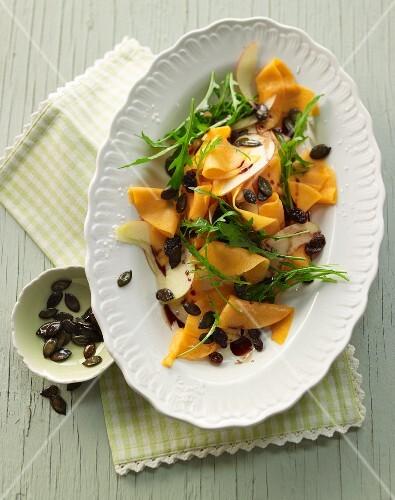 Raw marinated pumpkin salad with rocket, apple, pumpkin seeds and pumpkin seed oil
