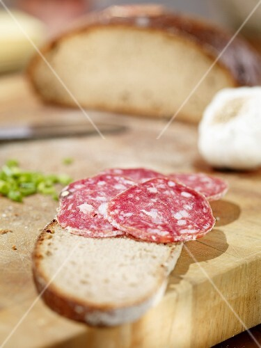 A slice of bread topped with salami on a wooden board