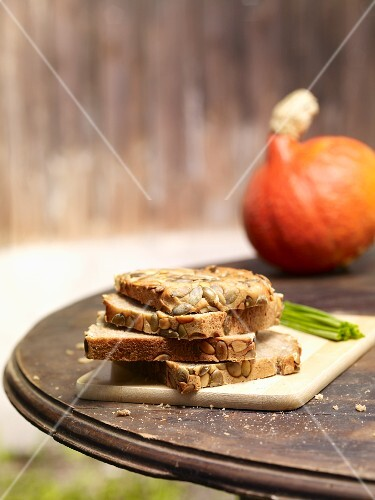 Slices of pumpkin seed bread, stacked, on a rustic garden table