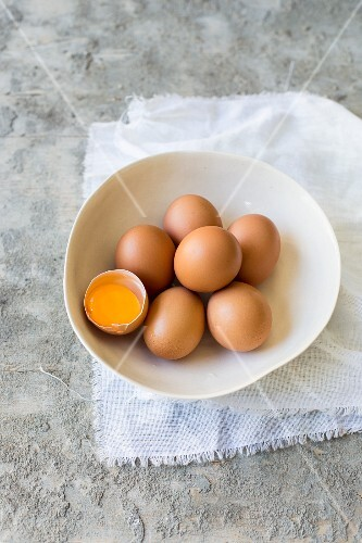 Large brown organic eggs, one cracked open, in a bowl