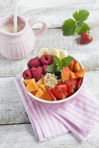A bowl of quinoa, fresh fruit and mint leaves, a jug of milk and a strawberry with a leaf