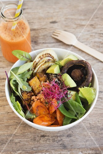 Quinoa salad with fried tofu, vegetables and mushrooms with a bottle of carrot juice