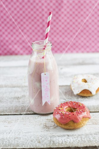 A bottle of strawberry milk with yoghurt spots and mini iced doughnuts