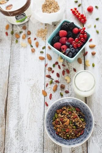 A muesli mixture, yoghurt, fresh berries and a jar of coconut fat