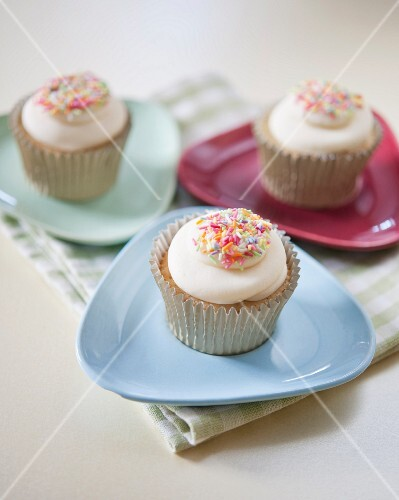 Vanilla cupcakes decorated with coloured sugar sprinkles