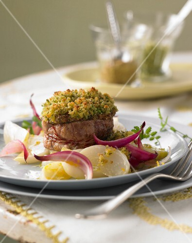 Pork medallions with a wild herb crust on May turnips in orange