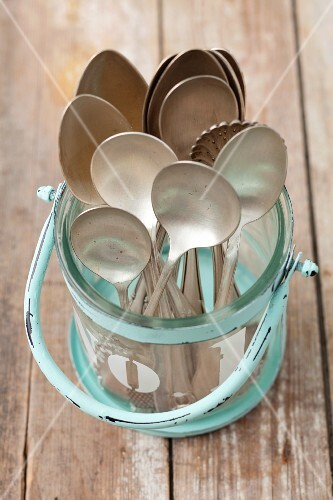 Old spoons in a glass container