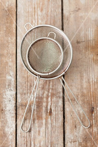 Old metal sieves on a wooden surface