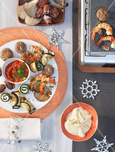Cooking at a table: tapas on a hot stone with various dips