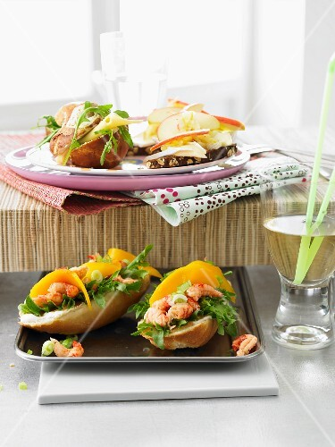 Snacks for a party buffet: a rocket roll, a slice of cheese and nut bread and crayfish baguettes