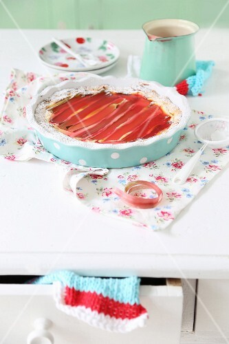 Rhubarb tart in turquoise flan dish on floral fabric
