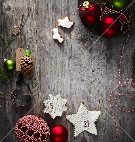 Stars cut out of book pages and other Christmas decorations on weathered wooden surface