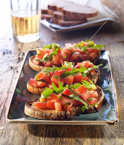 Bruschetta topped with tomato and rocket