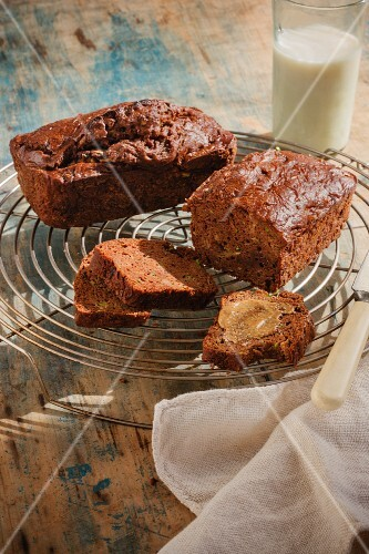 Banana bread, whole and sliced on a cooling rack