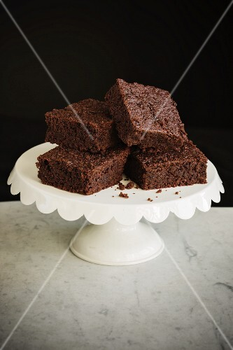Slices of chocolate and courgette tray bake cake on a cake stand